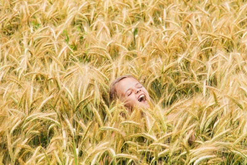 Mädchen, das auf dem Weizengebiet schreit lizenzfreie stockfotografie