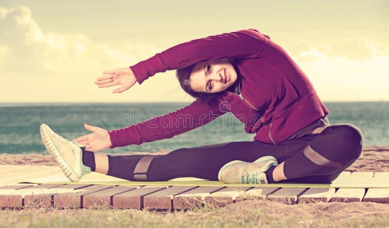 Mädchen, das auf der Übungsmatte im Freien trainiert stockbild