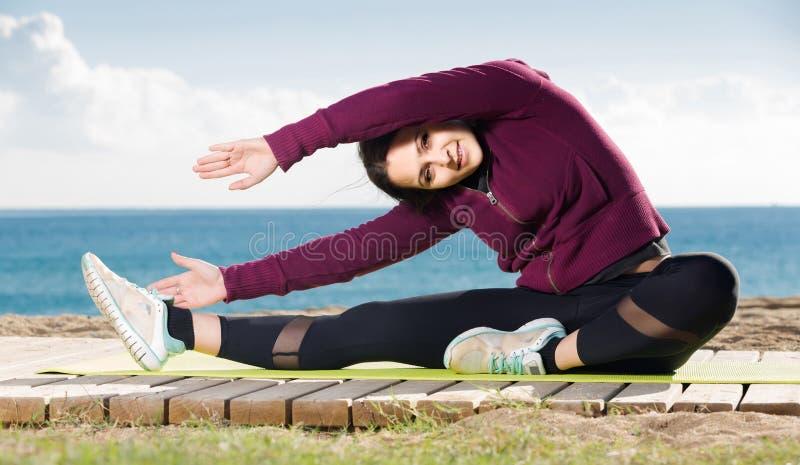 Mädchen, das auf der Übungsmatte im Freien trainiert lizenzfreies stockfoto