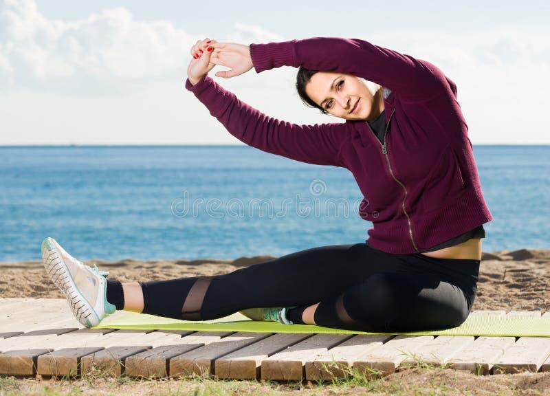 Mädchen, das auf der Übungsmatte im Freien trainiert stockbilder