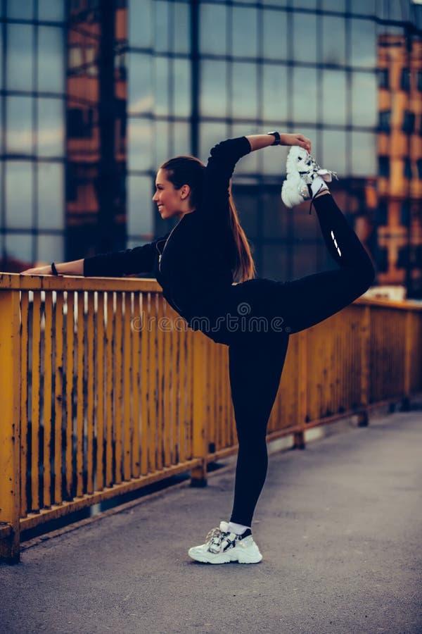 Mädchen, das auf der Flussbrücke, bereitend für die Glättung des Trainings aufwärmt vor lizenzfreies stockfoto