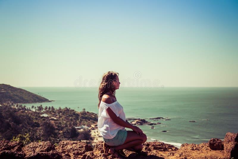 Mädchen, das auf der Wand des Forts auf dem Hintergrund des Strandes Vagator sitzt stockfoto
