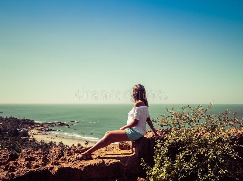 Mädchen, das auf der Wand des Forts auf dem Hintergrund des Strandes Vagator sitzt stockbild