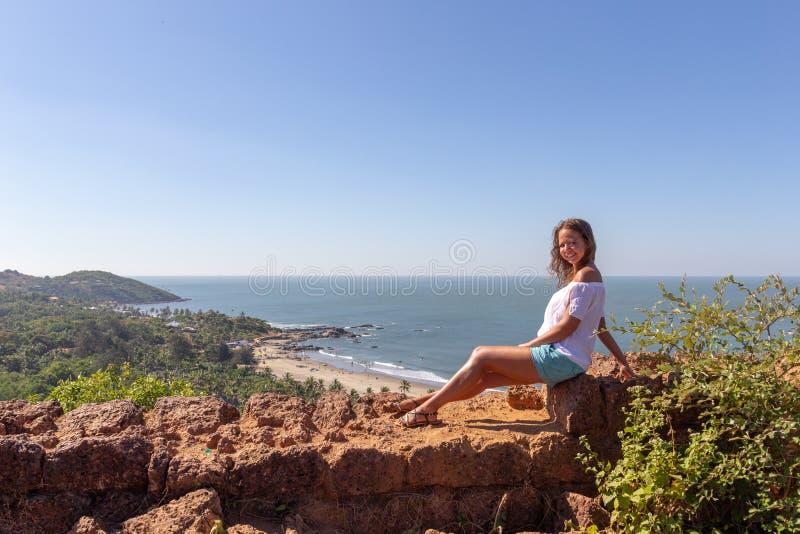 Mädchen, das auf der Wand des Forts auf dem Hintergrund des Strandes Vagator sitzt stockbilder