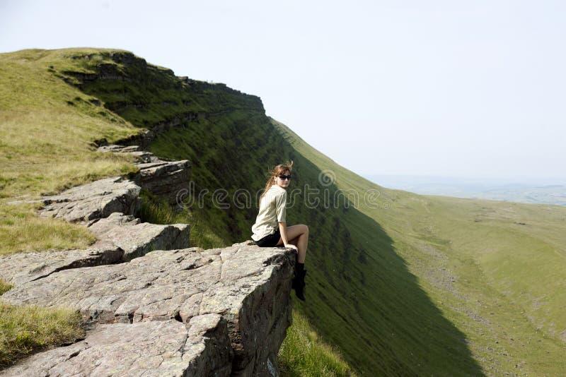 Mädchen, das auf die Oberseite der Klippe sitzt lizenzfreie stockfotos