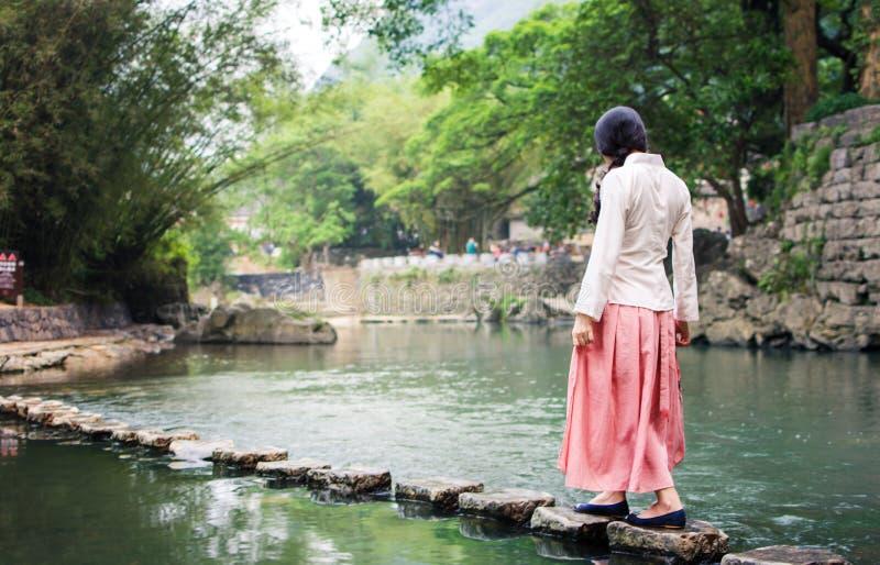Mädchen, das auf die Steinbrücke im Fluss geht stockfotografie