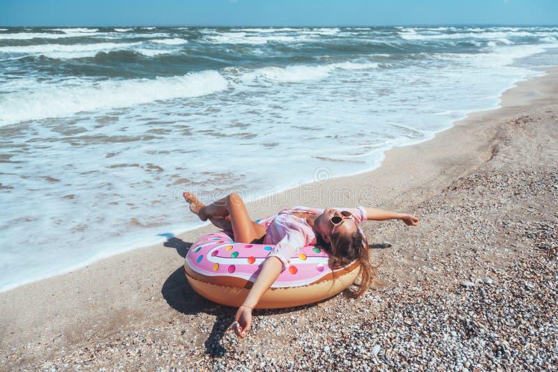 Mädchen, das auf Donut lilo auf dem Strand sich entspannt lizenzfreie stockfotografie