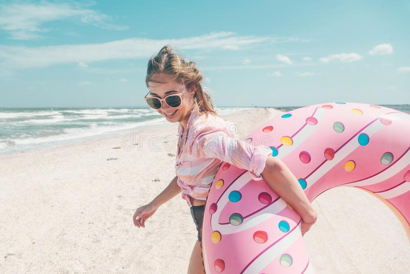 Mädchen, das auf Donut lilo auf dem Strand sich entspannt stockfotos