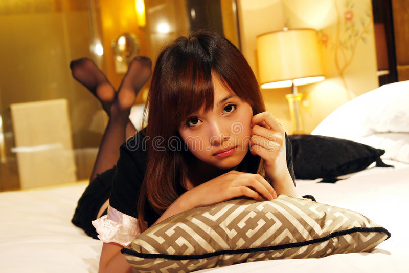 Mädchen, das auf einem Bett liegt stockbild