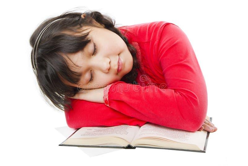 Mädchen, das auf einem Buch schläft lizenzfreie stockfotografie