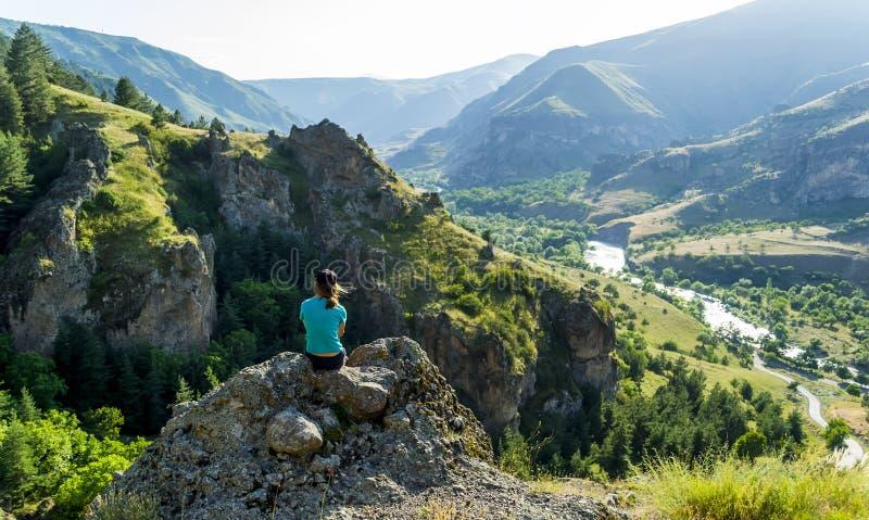 Mädchen, das auf einem Felsen betrachtet die Ansicht sitzt lizenzfreie stockbilder