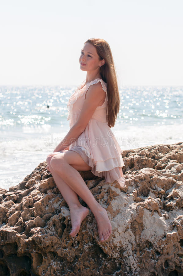 Mädchen, das auf einem Felsen sitzt stockfotos