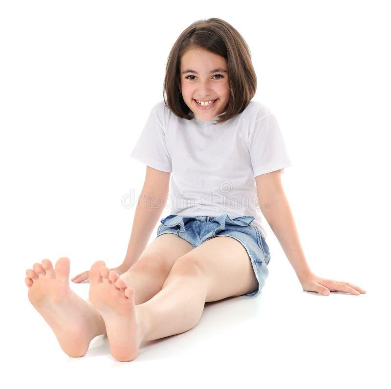Mädchen, das auf einem Fußboden sitzt stockbild