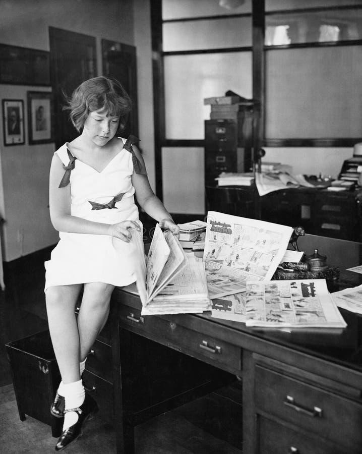 Mädchen, das auf einem Schreibtisch sitzt und eine Zeitung liest (alle dargestellten Personen sind nicht längeres lebendes und ke lizenzfreie stockfotografie