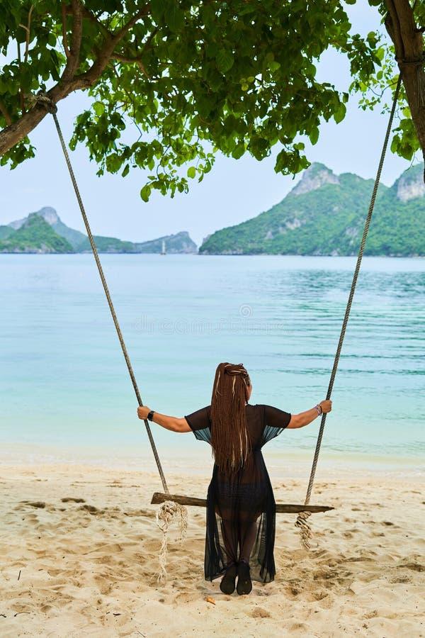 Mädchen, das auf einem Schwingen vor dem hintergrund der Inseln und der Bucht schwingt stockbilder