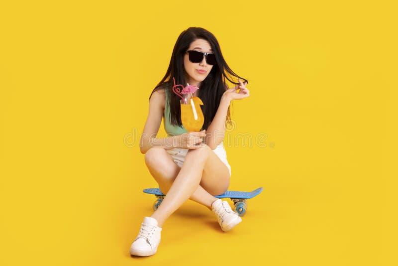 Mädchen, das auf einem Skateboard sitzt lizenzfreie stockbilder