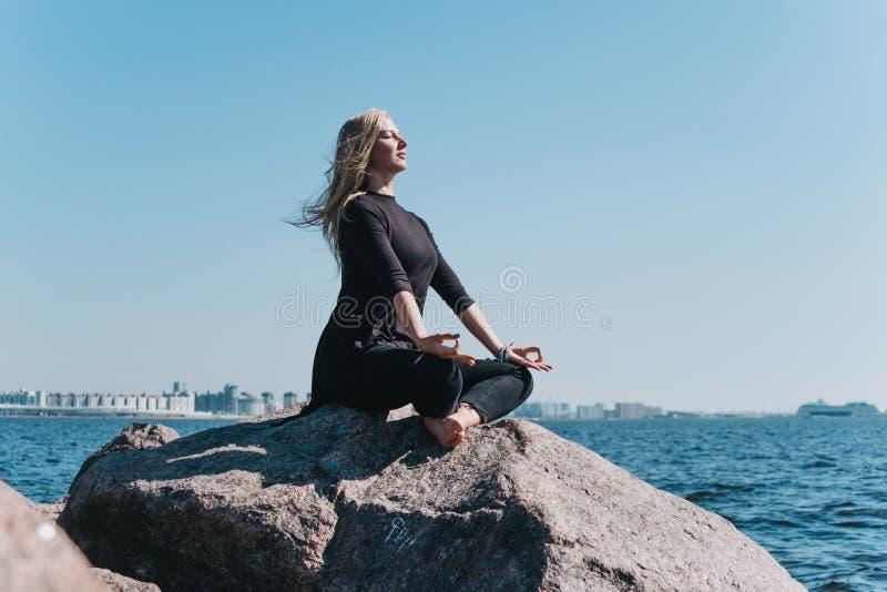 Mädchen, das auf einem Stein auf dem Meer meditiert stockbild