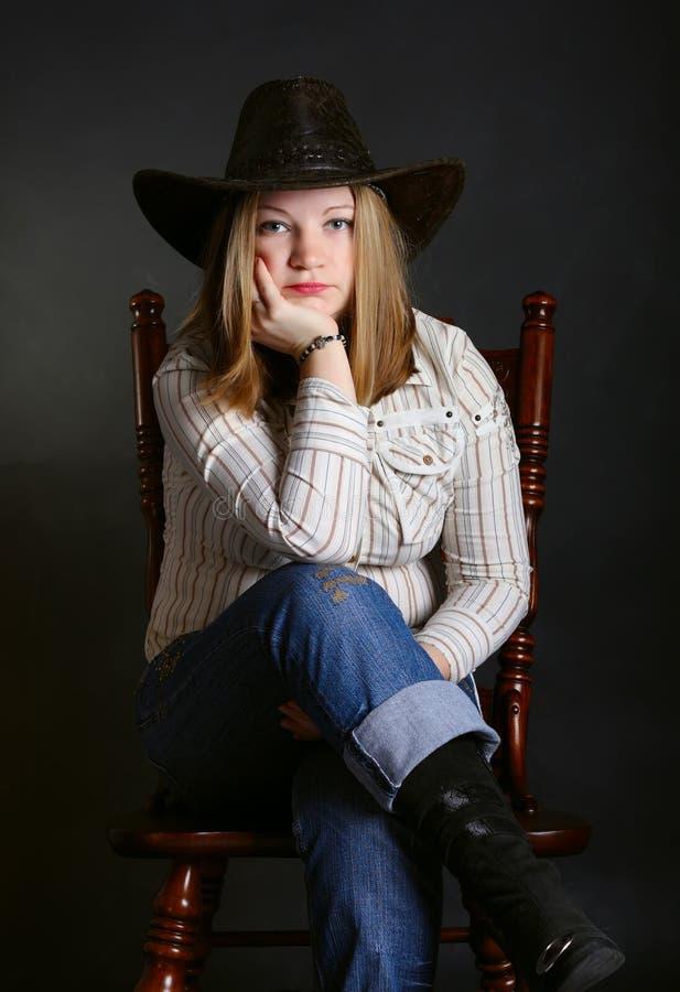 Mädchen, das auf einem Stuhl sitzt stockfotografie