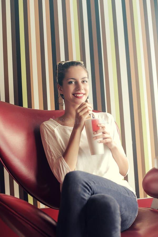 Mädchen, das auf einem Stuhl trinkt stockfotos