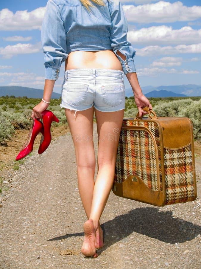 Mädchen, das auf einen Schotterweg mit einem Koffer geht lizenzfreie stockfotografie
