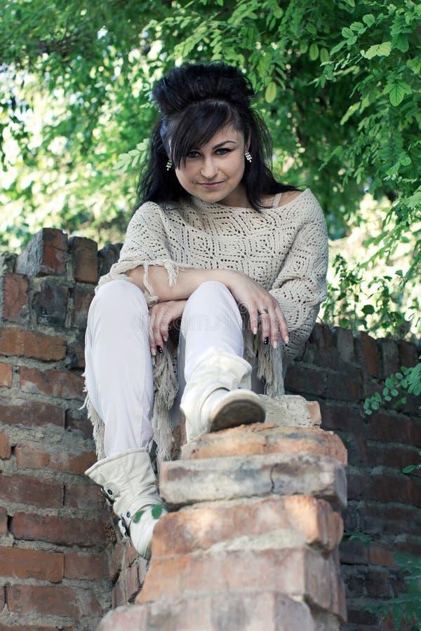 Mädchen, das auf einer Backsteinmauer sitzt stockfotos