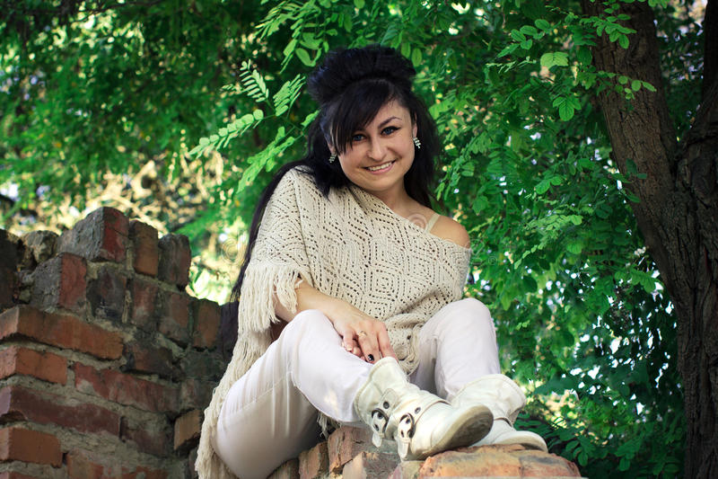 Mädchen, das auf einer Backsteinmauer sitzt stockfotografie