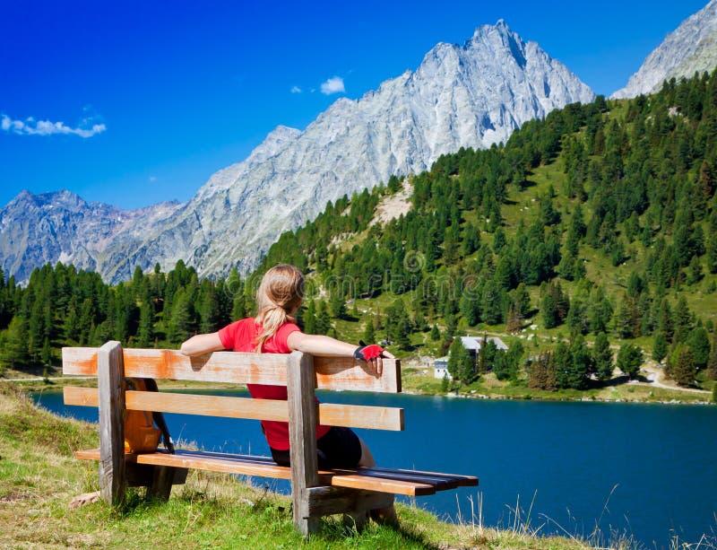 Mädchen, das auf einer Bank nahe dem See sitzt lizenzfreie stockbilder