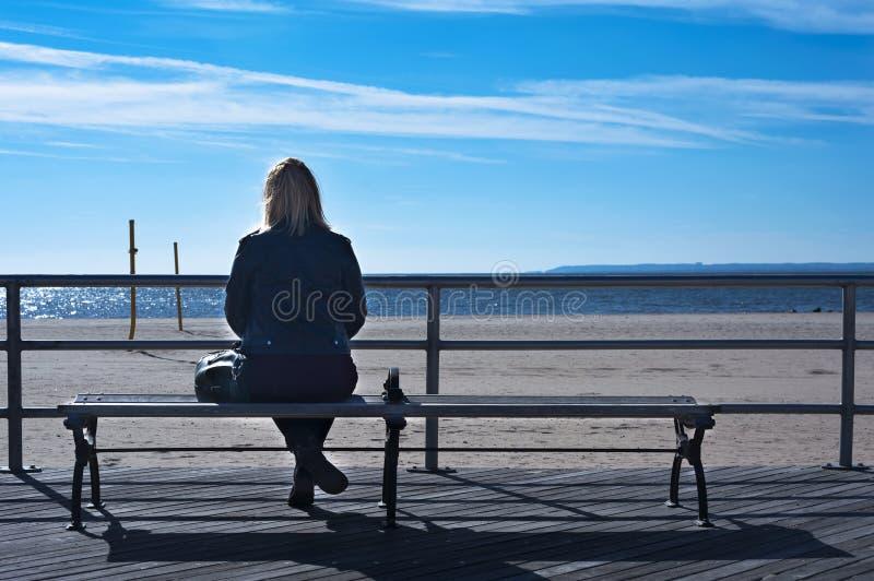 Mädchen, das auf einer Bank sitzt stockfotografie