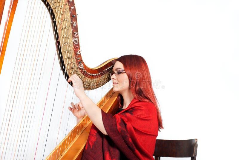 Mädchen, das auf einer Harfe spielt stockbild