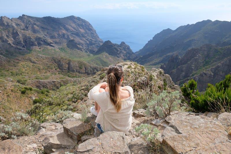 Mädchen, das auf einer Klippe schaut zu einem Tal sitzt stockbild