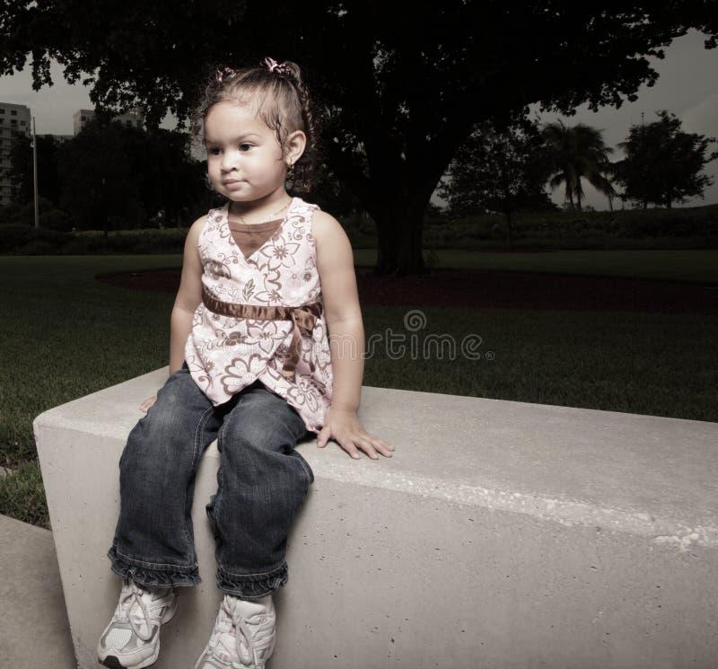 Mädchen, das auf einer Parkbank sitzt lizenzfreie stockbilder