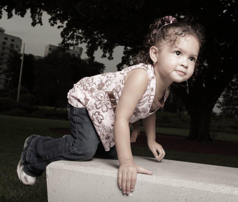 Mädchen, das auf einer Parkbank steigt lizenzfreie stockfotos