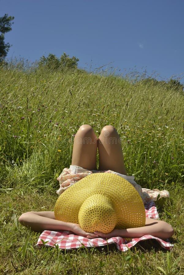 Mädchen, das auf grünem Gras liegt stockfotos