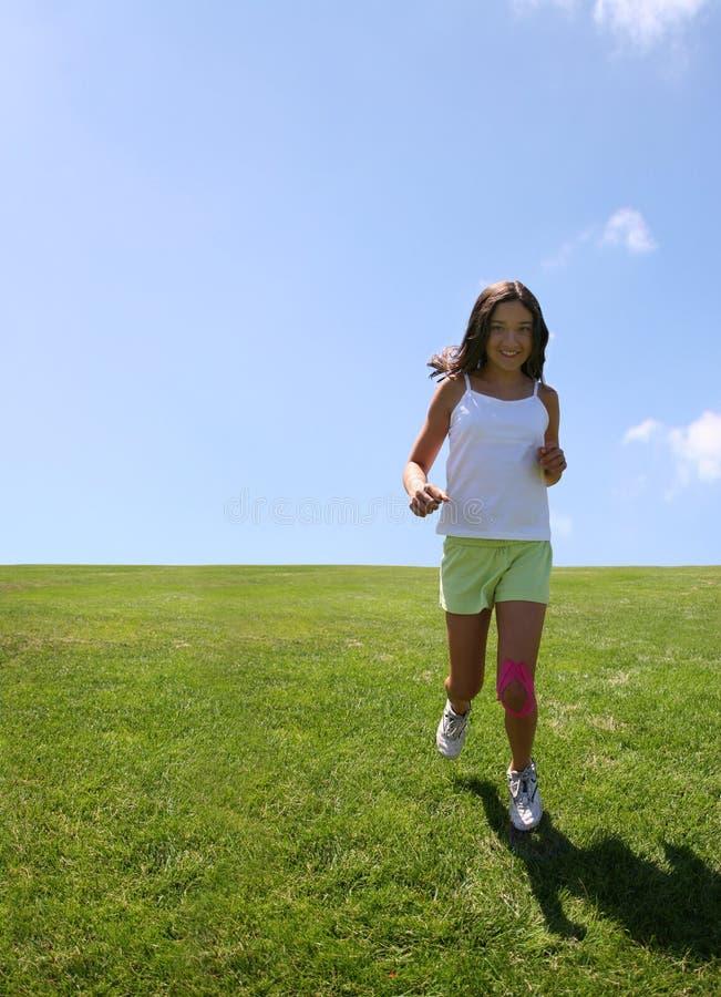 Mädchen, das auf Gras läuft lizenzfreie stockfotografie