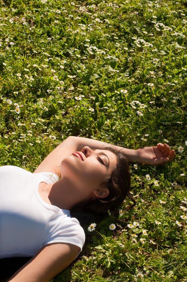 Mädchen, das auf Gras liegt lizenzfreie stockfotos