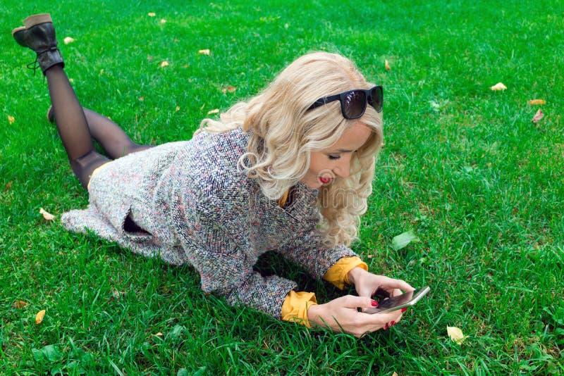 Mädchen, das auf Gras liegt und ein Telefon hält stockfoto