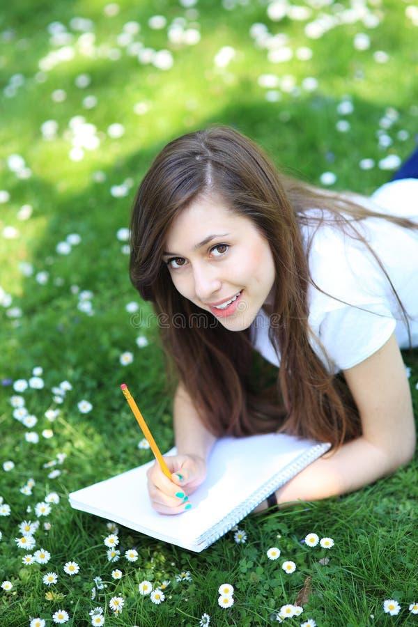 Mädchen, das auf Gras mit Übungsteil liegt stockfotografie