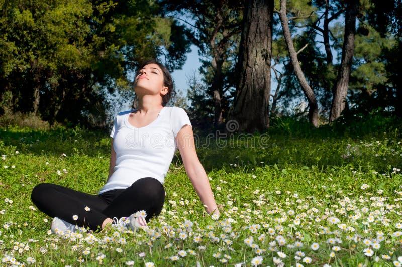 Mädchen, das auf Gras sitzt lizenzfreie stockfotos