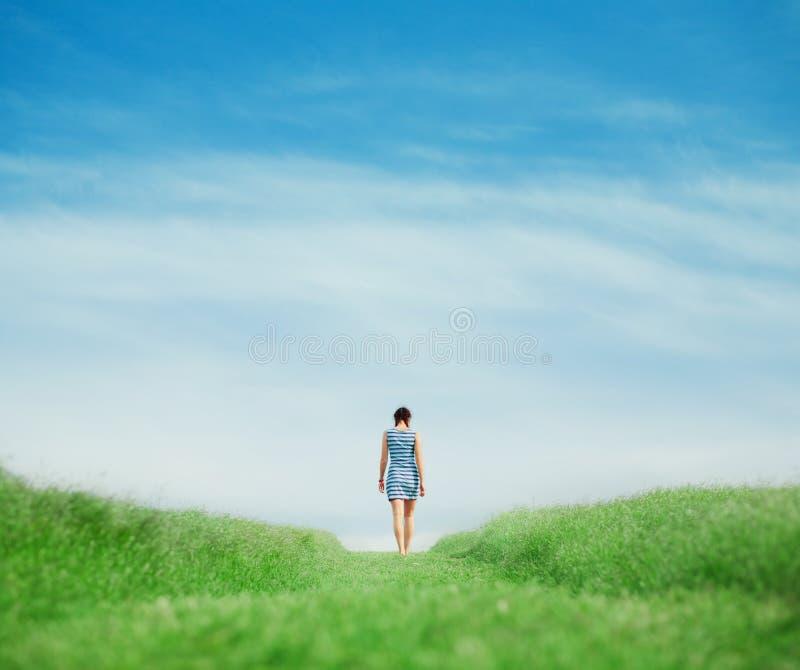 Mädchen, das auf Grasfeld geht lizenzfreie stockfotografie