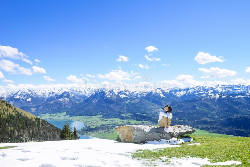 Mädchen, das auf großem Felsen, Schafberg-Berg, Österreich sitzt lizenzfreies stockbild