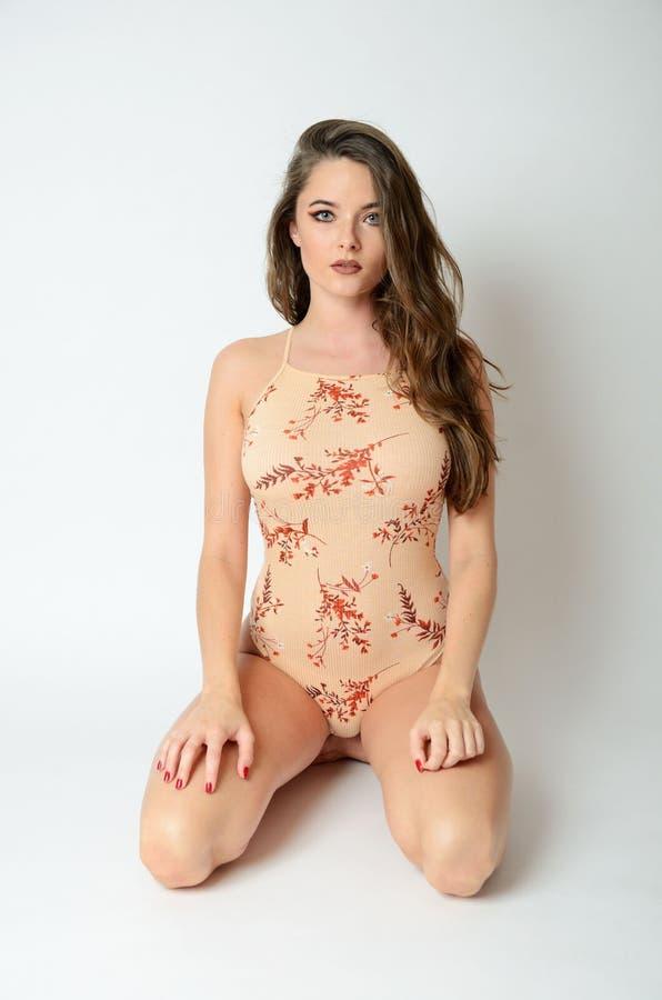 Mädchen, das auf ihren Knien sitzt stockfotografie