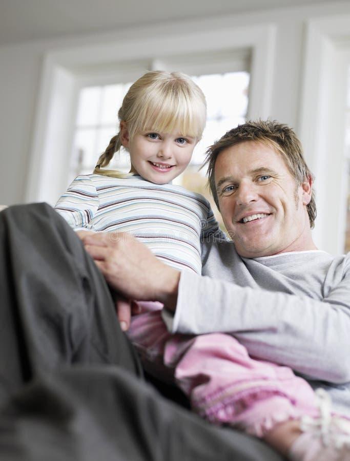 Mädchen, das auf Lap In House des Vaters sitzt lizenzfreies stockfoto