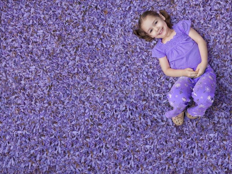 Mädchen, das auf purpurroten Blumen liegt lizenzfreies stockfoto