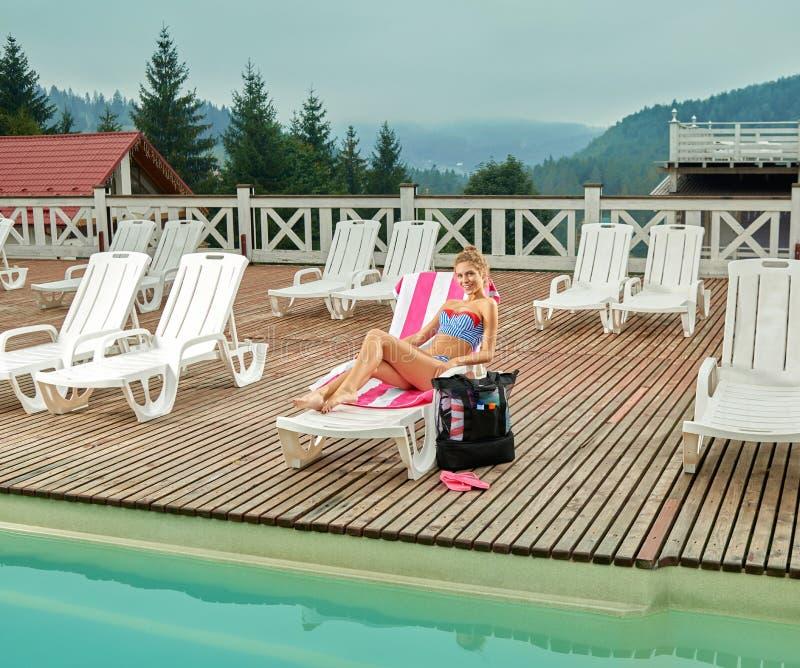 Mädchen, das auf Ruhesessel nahe Pool liegt und sich tagsüber bräunt lizenzfreies stockfoto