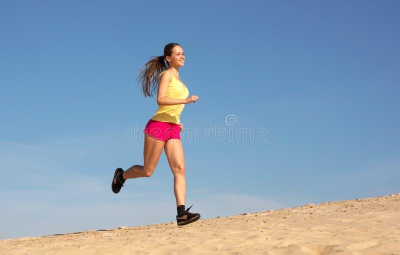 Mädchen, das auf Sand läuft stockfoto