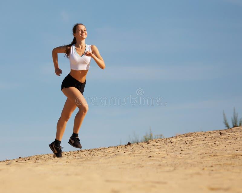 Mädchen, das auf Sand läuft stockfotografie