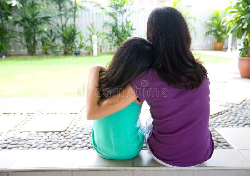 Mädchen, das auf Schulter ihrer Schwester für suppor sich lehnt lizenzfreie stockfotos