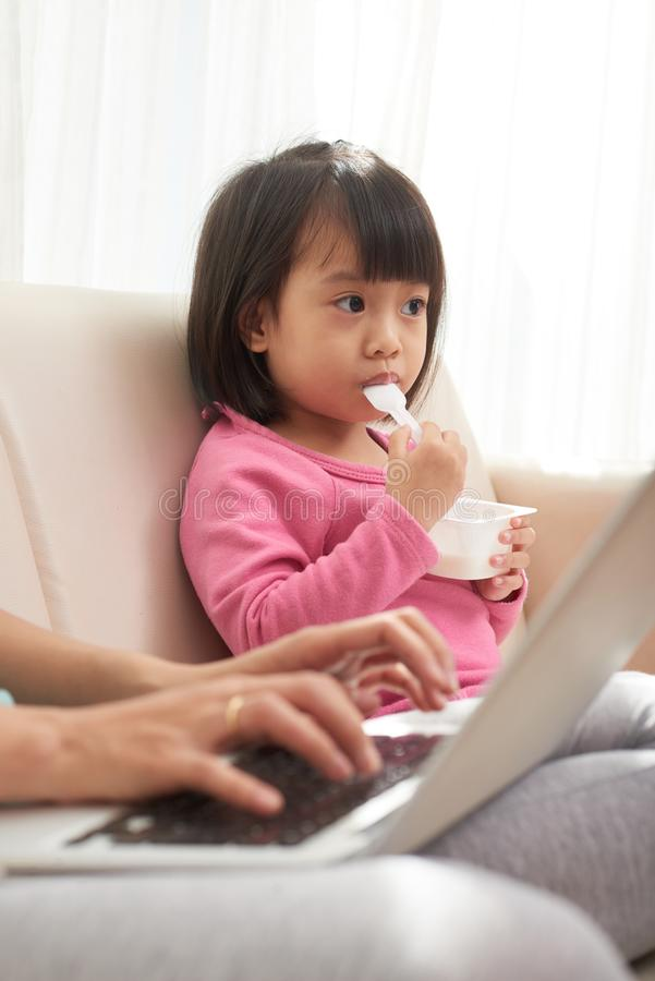 Mädchen, das auf Sofa mit berufstätiger Mutter isst lizenzfreies stockfoto