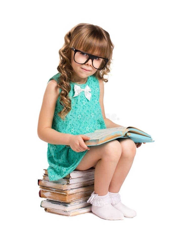 Mädchen, das auf Stapelbüchern stationiert stockfotos