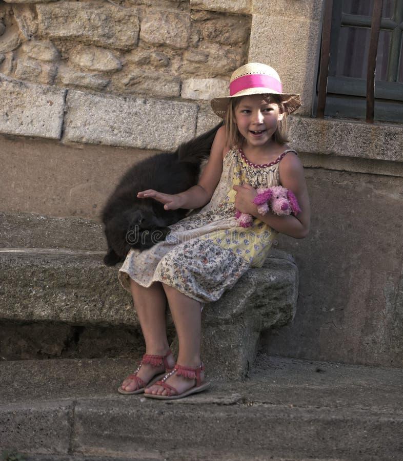 Mädchen, das auf Steinsitz sitzt stockfotos